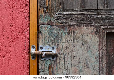 Closeup Of Red Wall And Vintage Door Locked With Latch