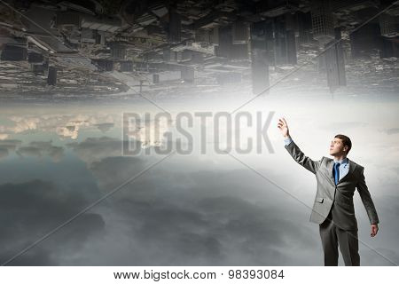 Businessman reaching his arm up to touch something