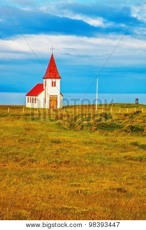 White  Chapel with red roof on the northern fjord. Iceland