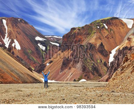 Smooth orange rhyolite mountains in Landmannalaugar nature reserve. The woman - tourist in blue jacket, raised her hands in delight