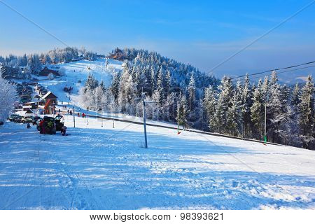 Winter mountain sports resort. Christmas in the forest.  Rolled ski trail glitters in sunny December day