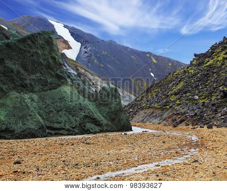 Green stone cliff and creek in the gorge. In the hollows lie snowfields. National Park Landmannalaugar in Iceland