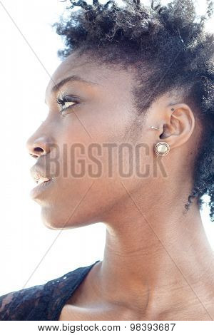 Attractive African woman with curly afro hair turning to look to the side with parted lips in a sensual beauty portrait, low angle on white