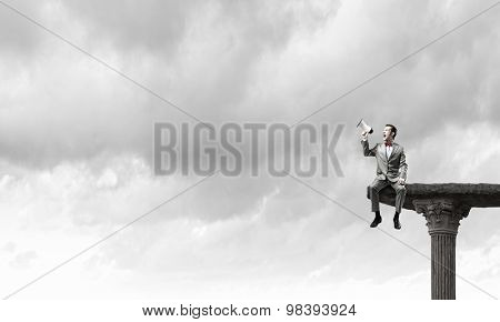 Businessman sitting on top and screaming in megaphone