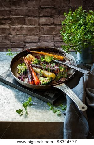 roasted rainbow carrot and broccoli in a vintage pan, rustic style