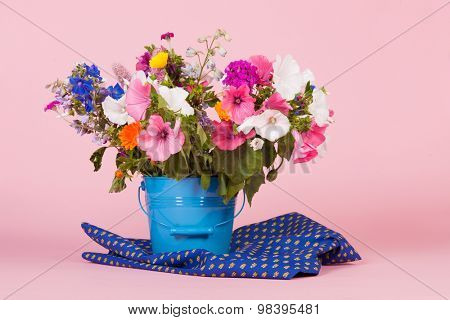 colorful summer garden flowers in blue bucket on pink background