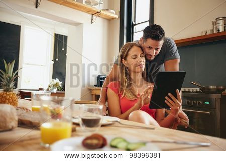 Couple In Kitchen Sharing An Interesting Site On Digital Tablet
