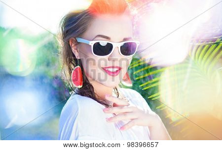Colorful summer portrait of happy young attractive woman wearing sunglasses and watermelon earrings, beauty and fashion concept natural bokeh and light effect