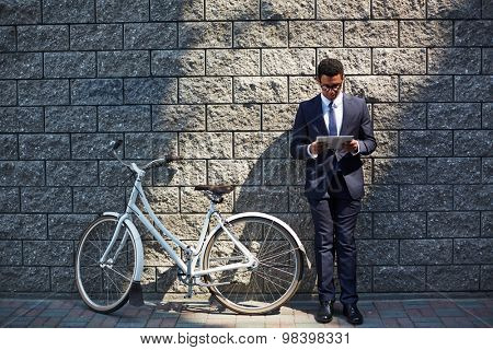 Handsome employee with touchpad networking by wall of modern building with bicycle near by