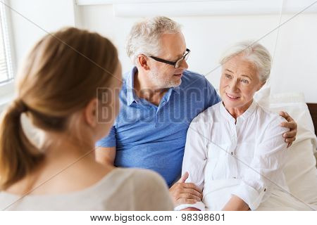 medicine, support, family health care and people concept - happy senior man and young woman visiting and cheering her grandmother lying in bed at hospital ward
