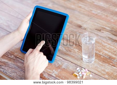 medicine, technology, nutritional supplements and people concept - close up of male hands pointing finger to blank tablet pc computer screen, pills and water on table