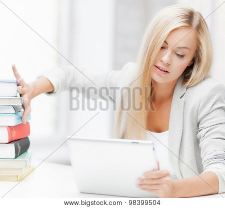 student with tablet pc pushing away stack of books