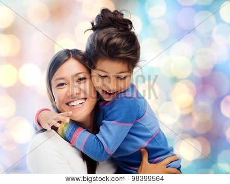 people, motherhood, family and adoption concept - happy mother and daughter hugging over blue holidays lights background