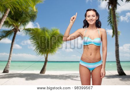 people, travel, swimwear and summer concept - happy young woman in bikini swimsuit pointing finger up to something imaginary over tropical beach with palm trees background