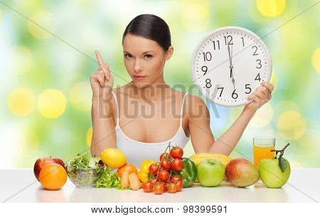 people, eating and diet concept - woman with healthy food holding big clock, pointing finger up and warning over green lights background