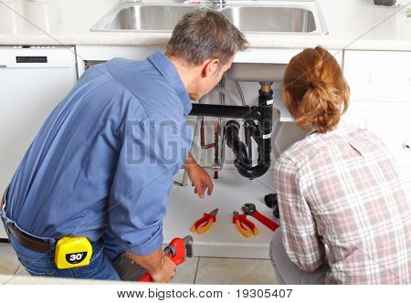 Young smiling plumber repairing sink in kitchen.