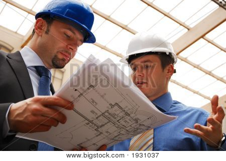 Two Architects Reviewing The Blueprints