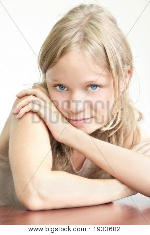 Beautiful Young Girl With Her Hands On The Table