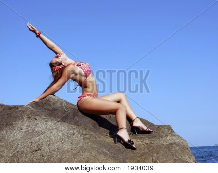 The Sexual Girl Sits On A Rock On A Background Of The Sky2