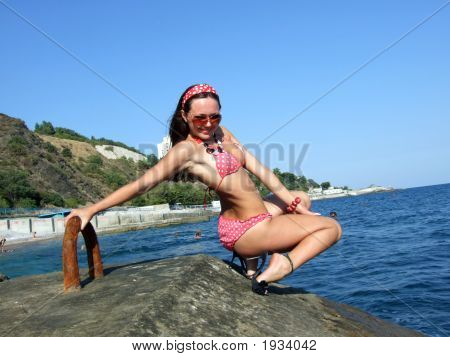 The Sexual Girl Sits On A Wharf On A Background Of The Sea