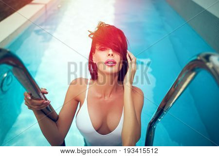 poster of Sexy wet woman in swimsuit with big tits at summer in swimming pool