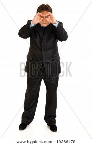 Full length portrait of interested businessman making binoculars with hands and looking through