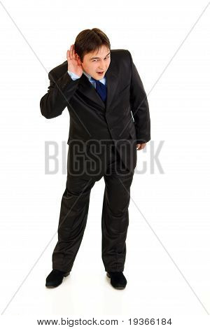 Full length portrait of stressful businessman holding hand at ear and listening isolated on white