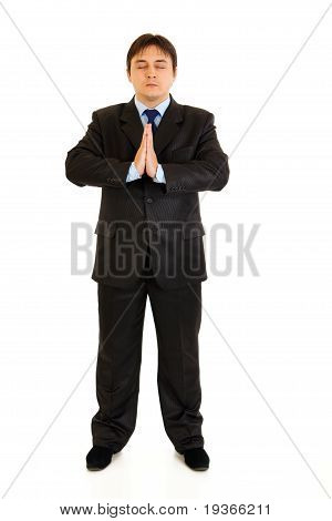 Full length portrait of praying businessman with closed eyes isolated on white