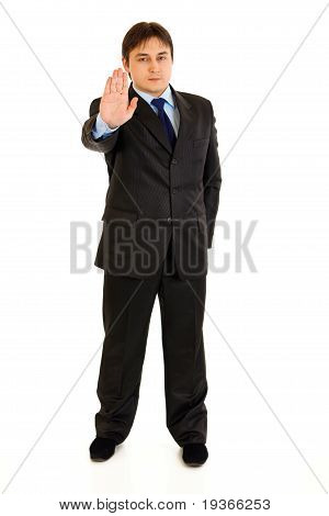 Full length portrait of confident modern businessman showing stop gesture isolated on white