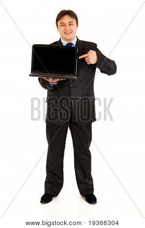 Full length portrait of smiling modern businessman pointing finger on laptops blank screen isolated