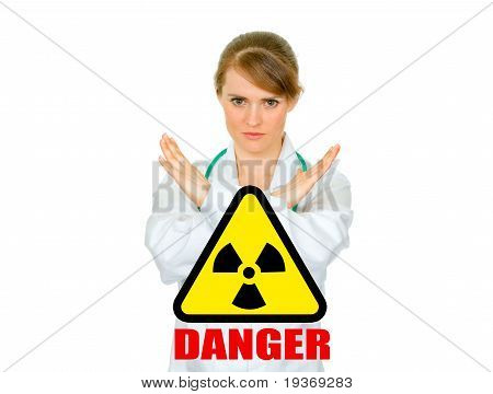 Concept-radiation hazard! Serious medical female doctor with crossed arms. Forbidden gesture.