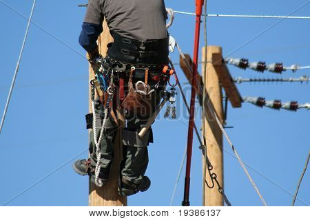 an electrical lineman apprentice working on a pole at a lineman college
