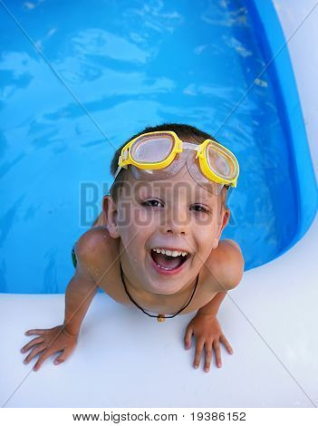a young boy swimming in a small pool