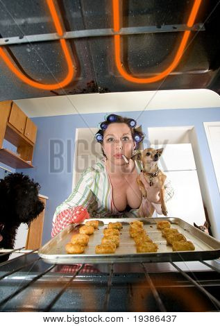 a woman pulling a pan out of the oven - domestic series