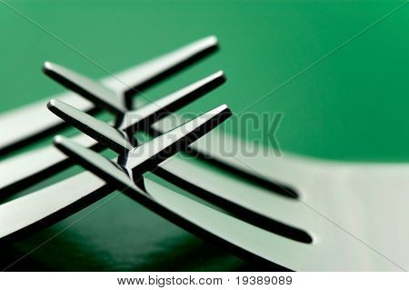 some silverware forks against a green background