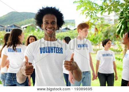 happy volunteer african american man showing thumbs up sign and group