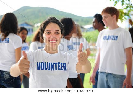 happy volunteer girl showing thumbs up sign, group in background