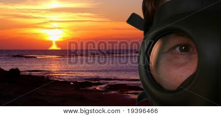 Explosion of a nuclear bomb and the person in a gas mask in the foreground