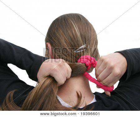 The girl fastens hair an elastic band