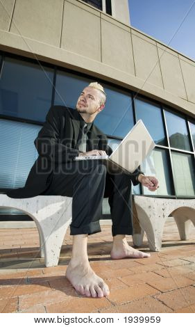 Barefoot Punk Businessman With His Laptop Computer