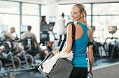 Fit woman holding gym bag in a fitness centre. Beautiful blonde woman ready to start her training. P poster