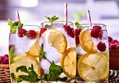 Cold non alcoholic cocktails with lemon slice and raspberries. Cold water with lemon and mint leaf.  poster