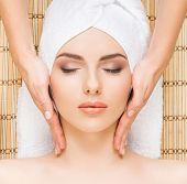Beautiful, young and healthy woman in spa salon on bamboo mat. Spa, health and healing concept. poster