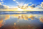 stock photo of sunset beach  - Spectacular golden sunrise over ocean with beach in foreground - JPG