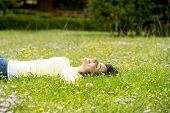 Happy Beautiful Latin Woman Lying On The Green Grass Sleeping And Meditating poster