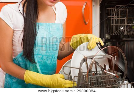 Attractive brunette woman cleaning kitchen using dish washing machine.