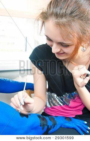 Girl Making A Bodyart Painting On Hand Of Young Caucasian Handsome