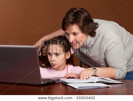 Woman and Child working homework on a laptop