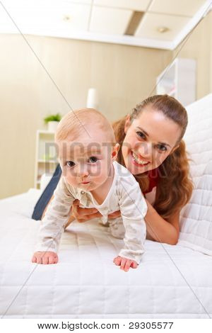 Happy Mother And Interested Baby Playing On Divan