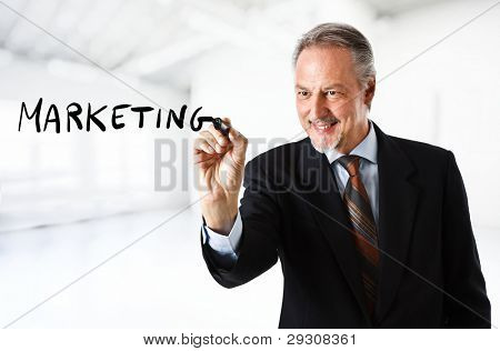 Businessman writing the word marketing on the screen